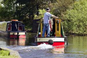 a narrowboat being steered along the oxford canal in the summer