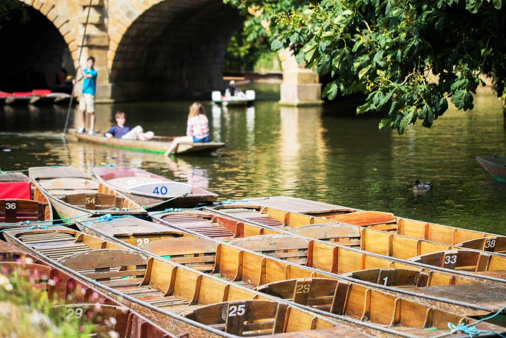 punting boats lined up next to a thames river bridge