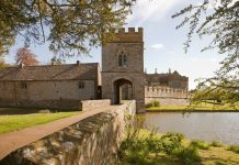 broughton castle entrance in the summer with a bridge over the moat