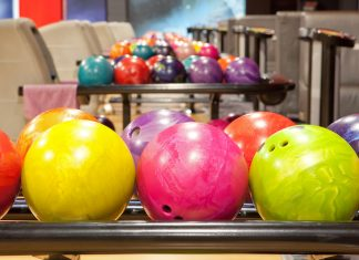 colourful bowling balls lined up in a bowling alley