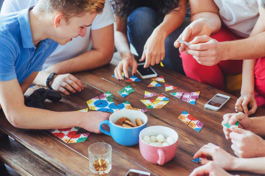 a group of friends playing a board game at a gaming hub cafe