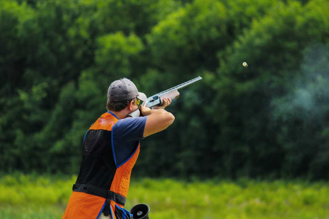 a man firing his rifle at a clay pigeon in the countryside