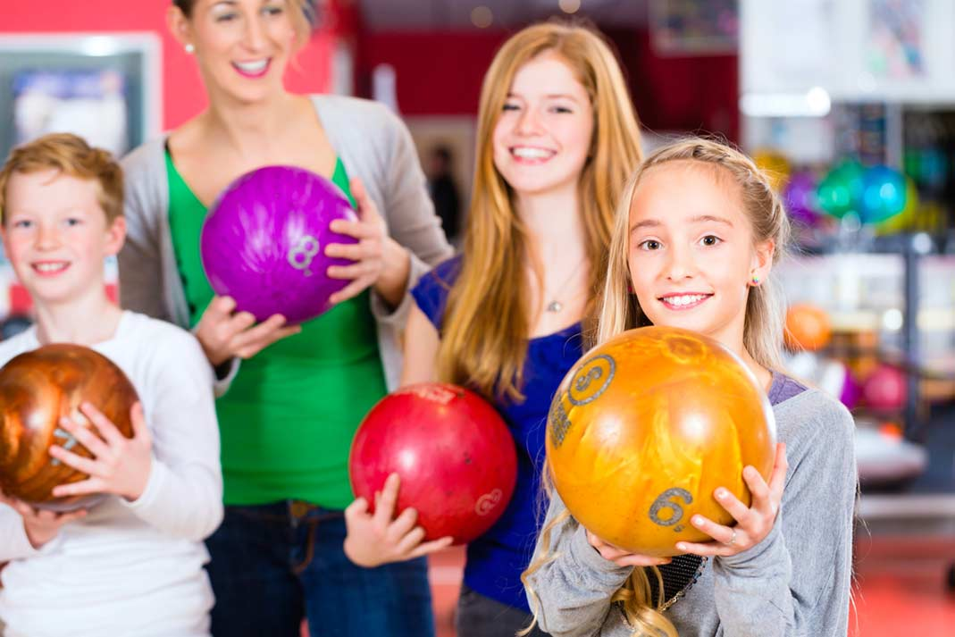 a family holding up bowling balls at a 10 pin bowling alley