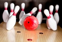 a bowling ball striking pins at a 10 pin bowling alley