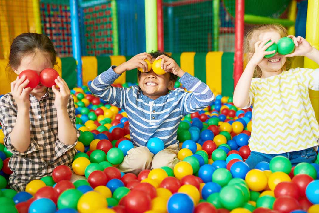 children playing happily in an indoor ball pit