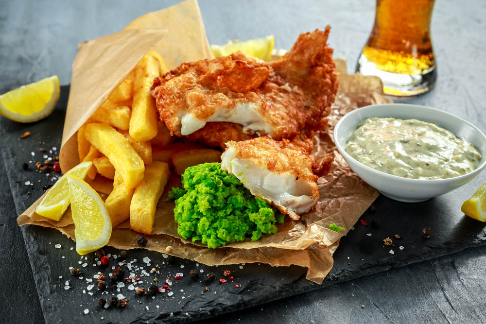 gourmet fish chips and mushy peas on slate