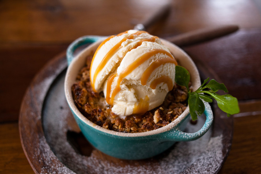 pot of apple crumble with toffee drizzle presented on a wooden table