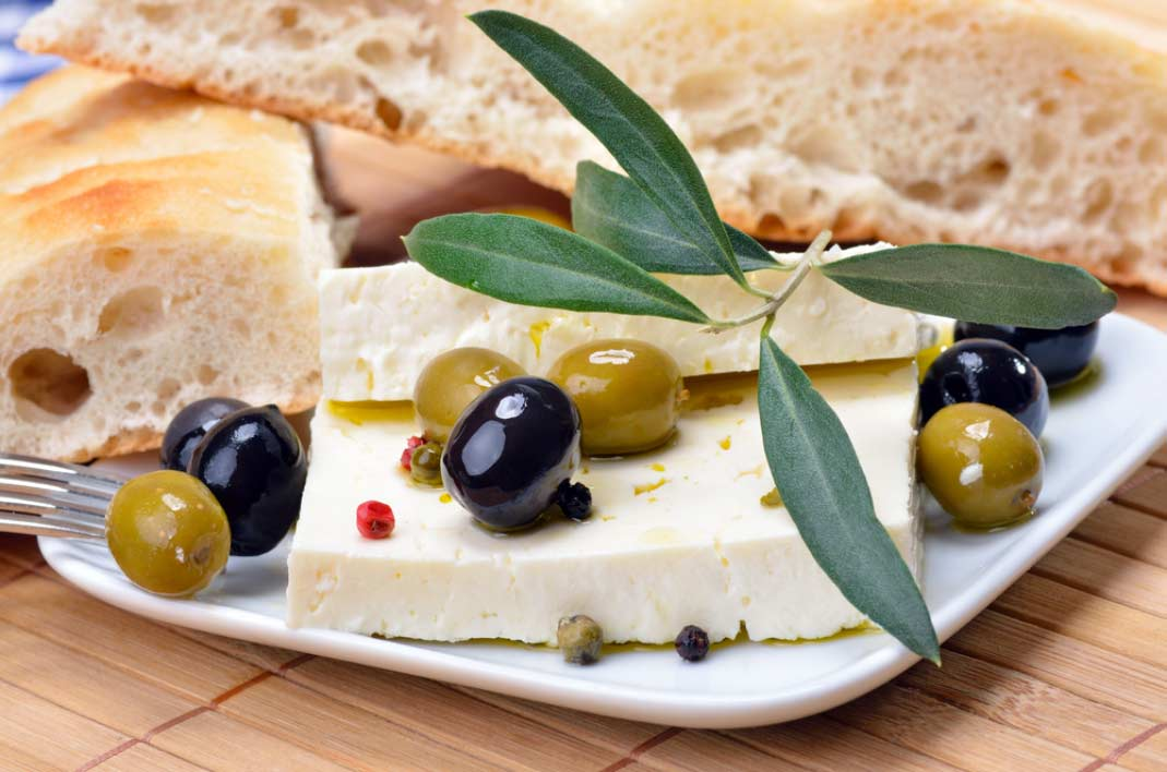 close up of Greek feta cheese, bread and olives on a table