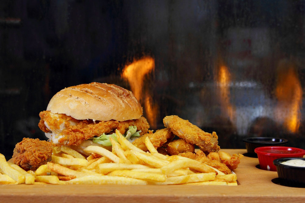 a burger with fried chicken and chips on a counter