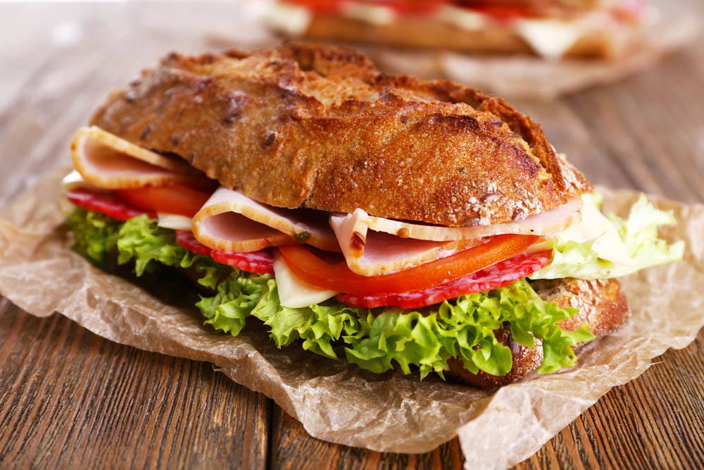 a rustic baguette filled with chicken and salad
