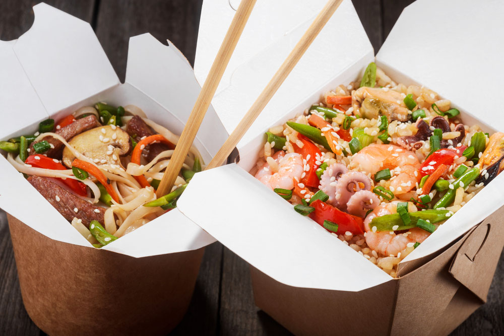 two takeaway boxes full of Chinese food with chopsticks