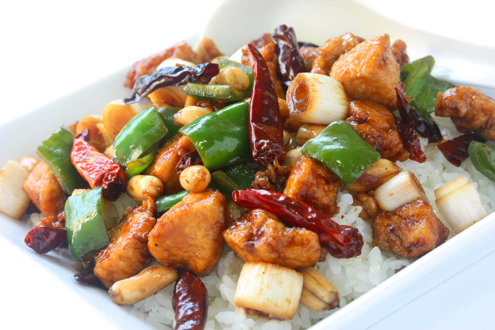 a plate of chinese chicken with vegetables and rice