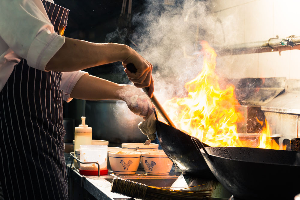 chef stir frying fiery Indian food in a professional kitchen