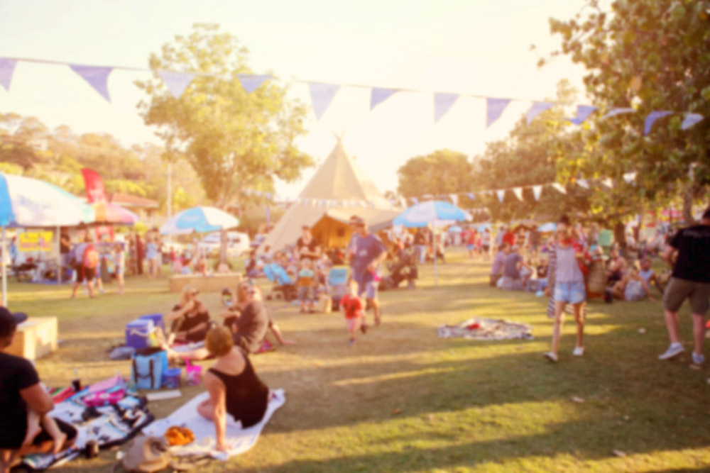 families having picnics amongst festival tents
