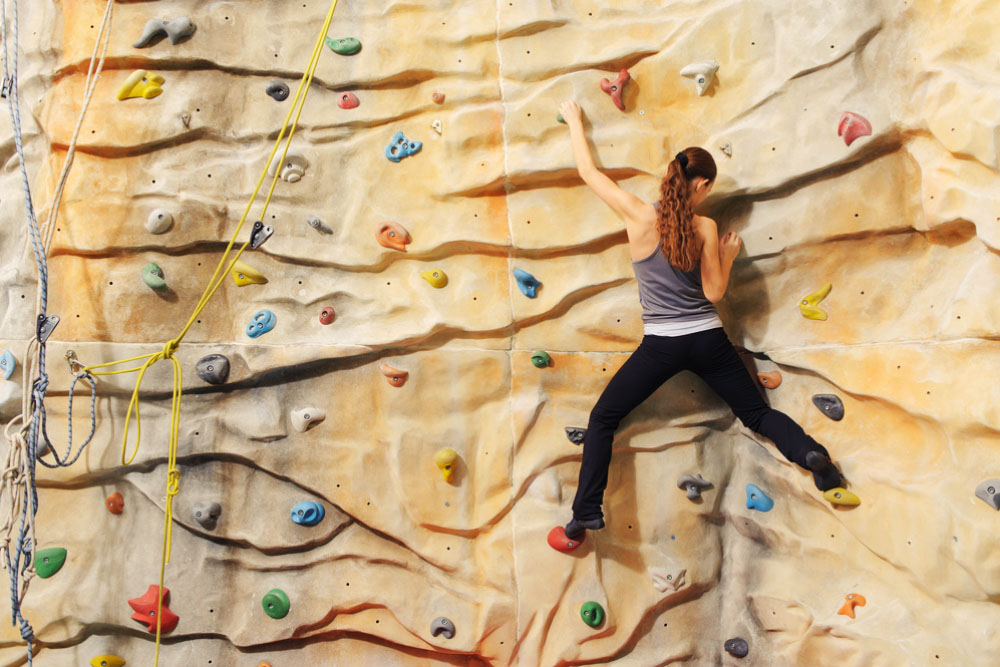 a woman climbing an indoor rock climbing wall