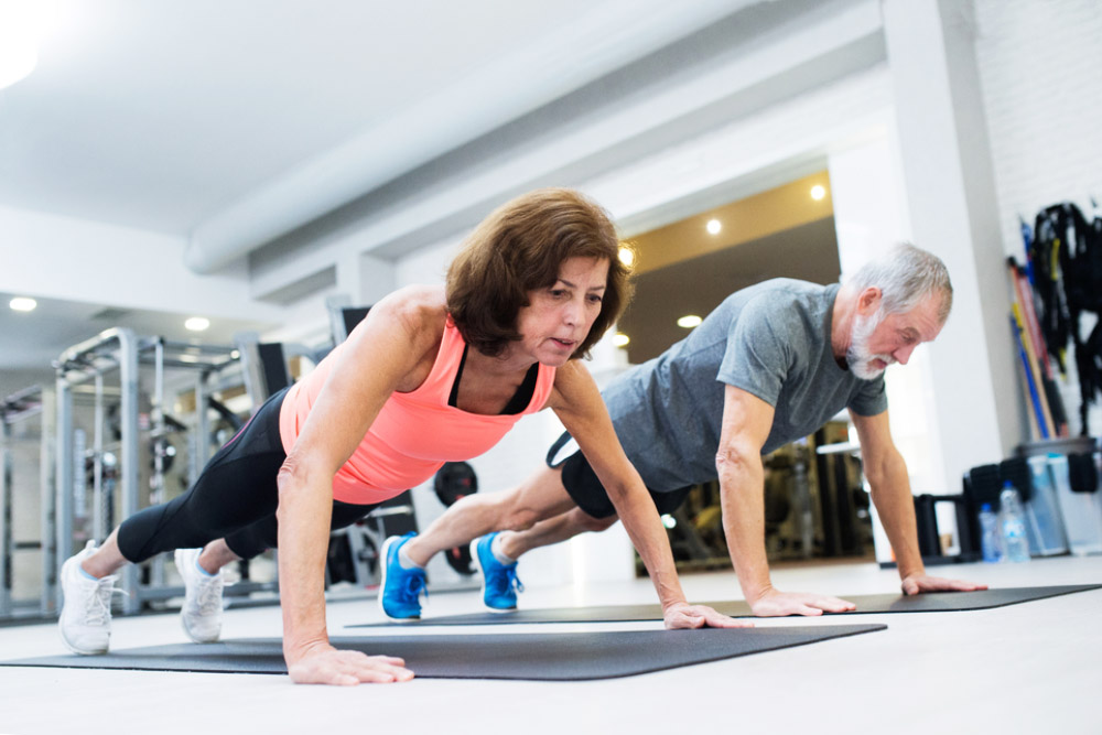 senior couple doing healthy push ups in a gym