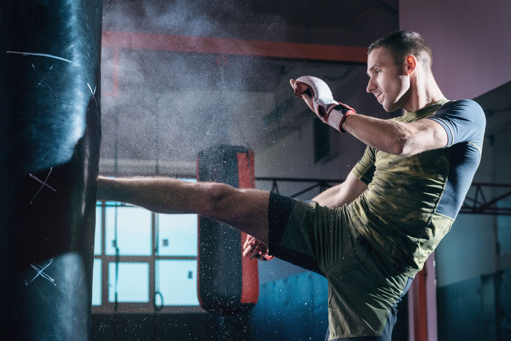 a man kickboxing in a fitness gym