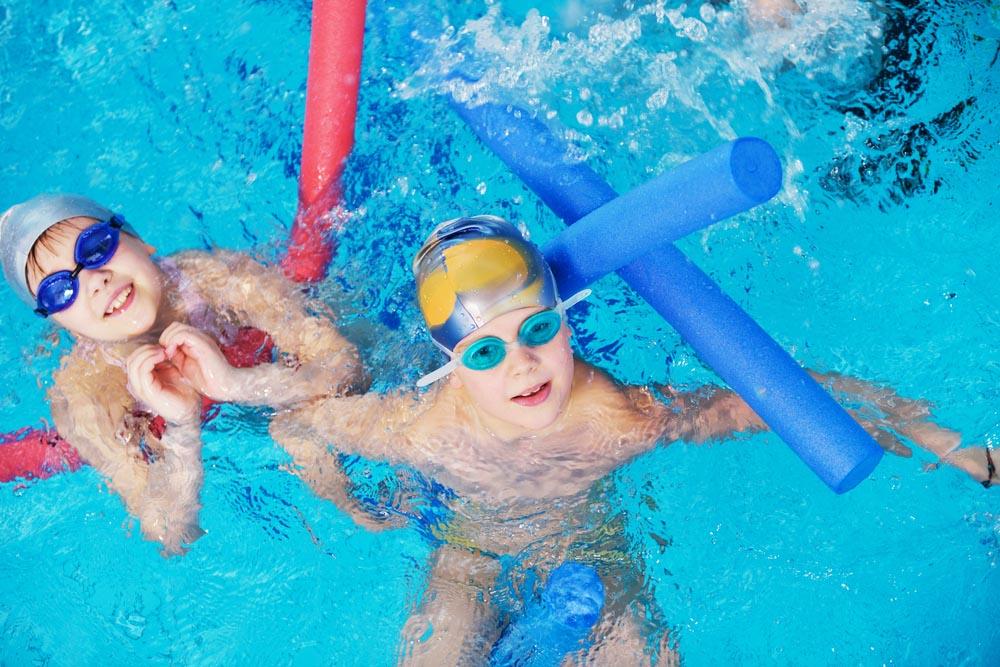 two kids having fun in an indoor swimming pool