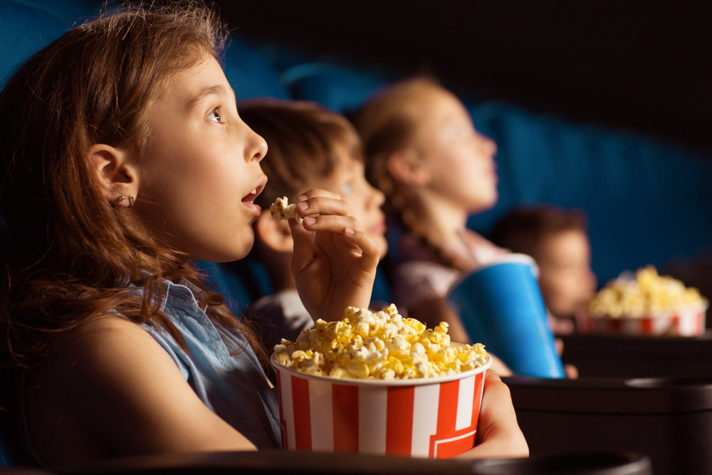 children watching movie at the cinema eating popcorn