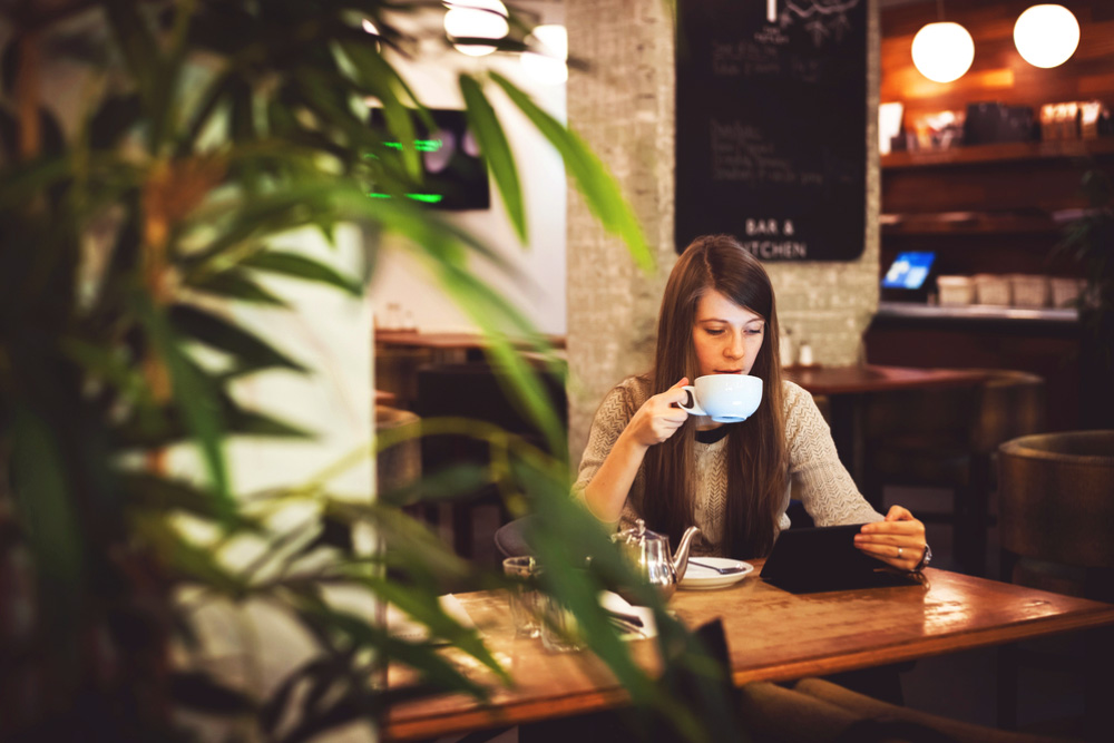 a young lady sat with a coffee and her laptop