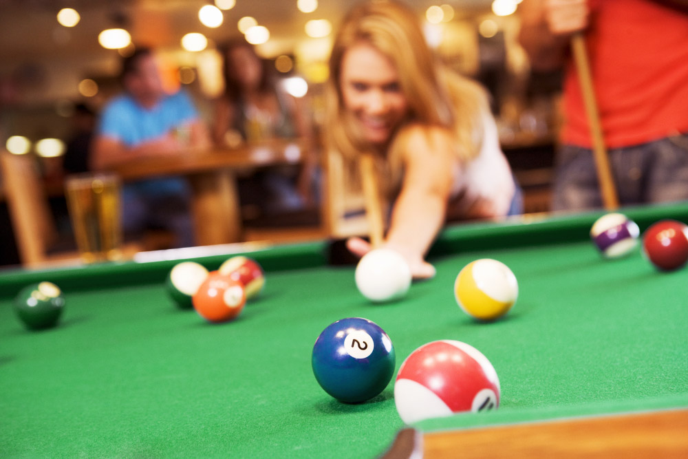 a young woman with friends playing pool