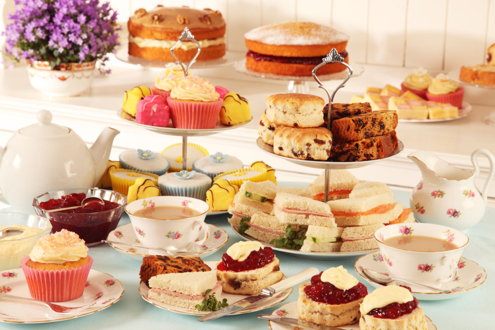 a delectable, colourful feast of cakes, sandwiches and scones with tea
