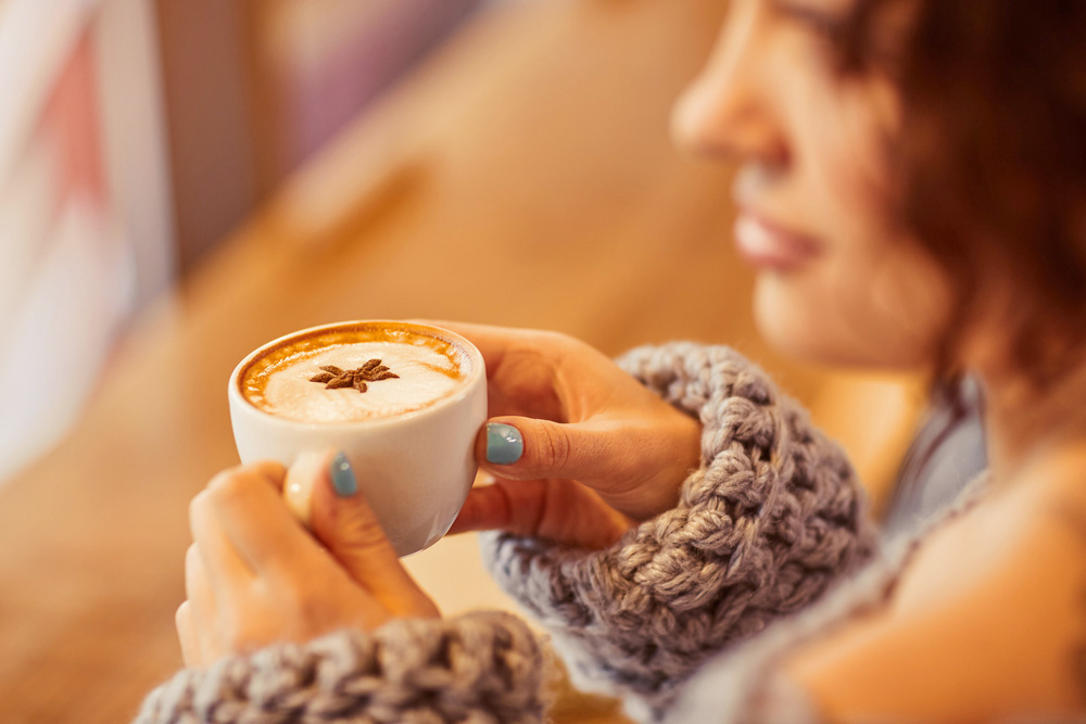 a woman holding a spiced latte inside a coffee shop