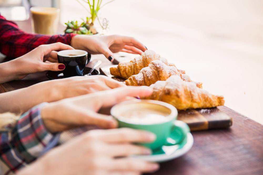a group of friends sharing coffee and croissants