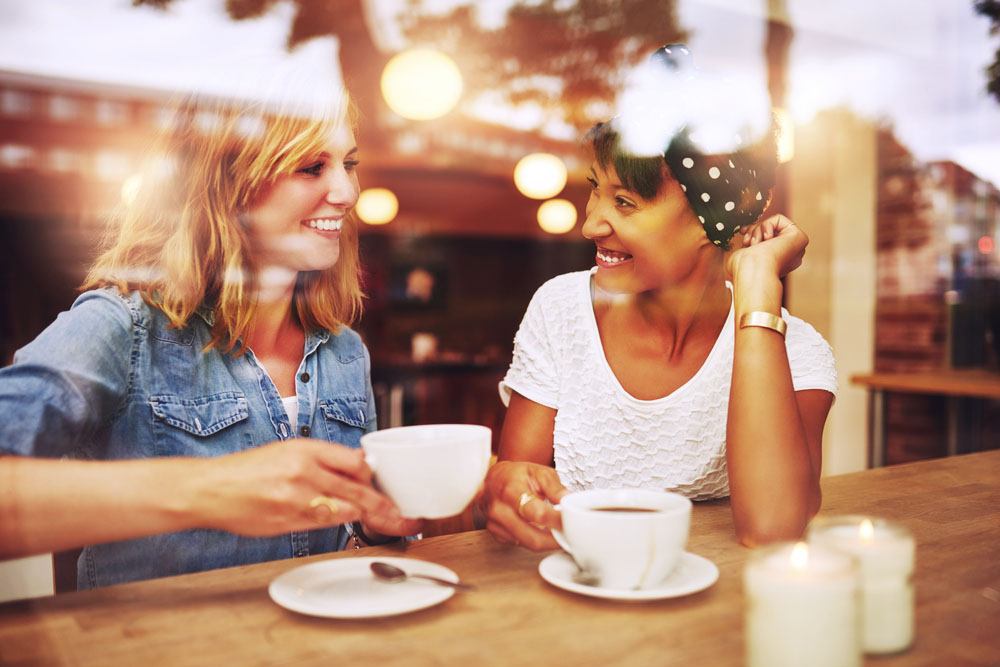 two women happily chatting as viewed through a coffee shop window