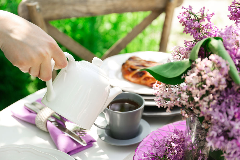 a pot of tea being poured outside in a sunny english garden