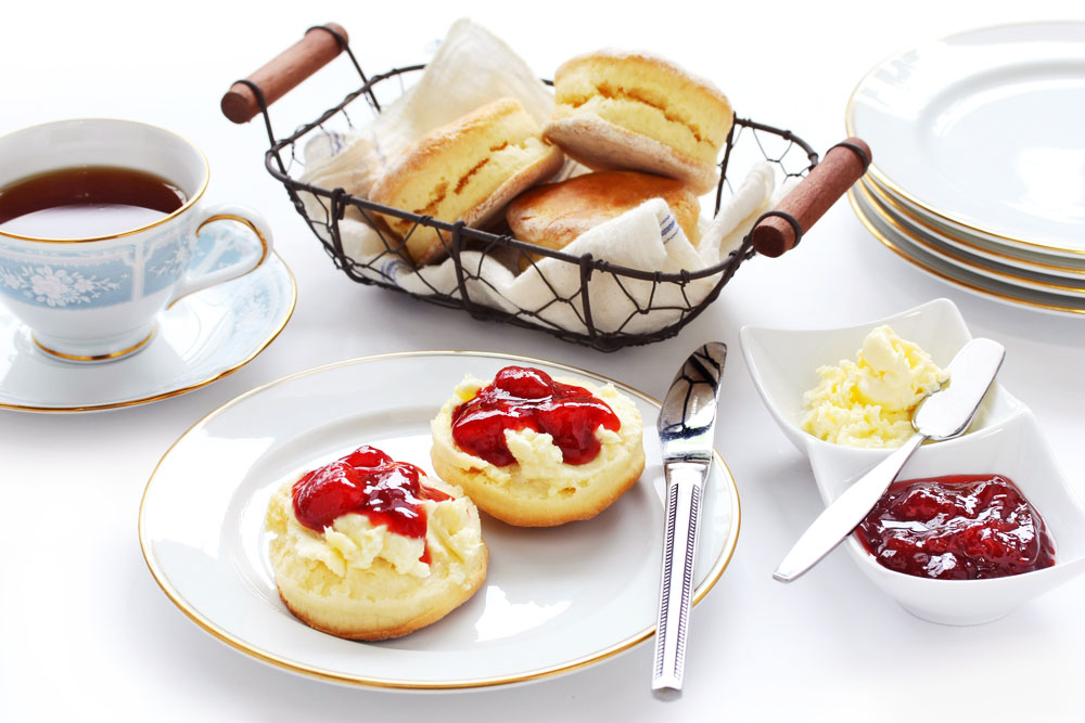 a spread of english jam and scones with tea presented in fine bone china
