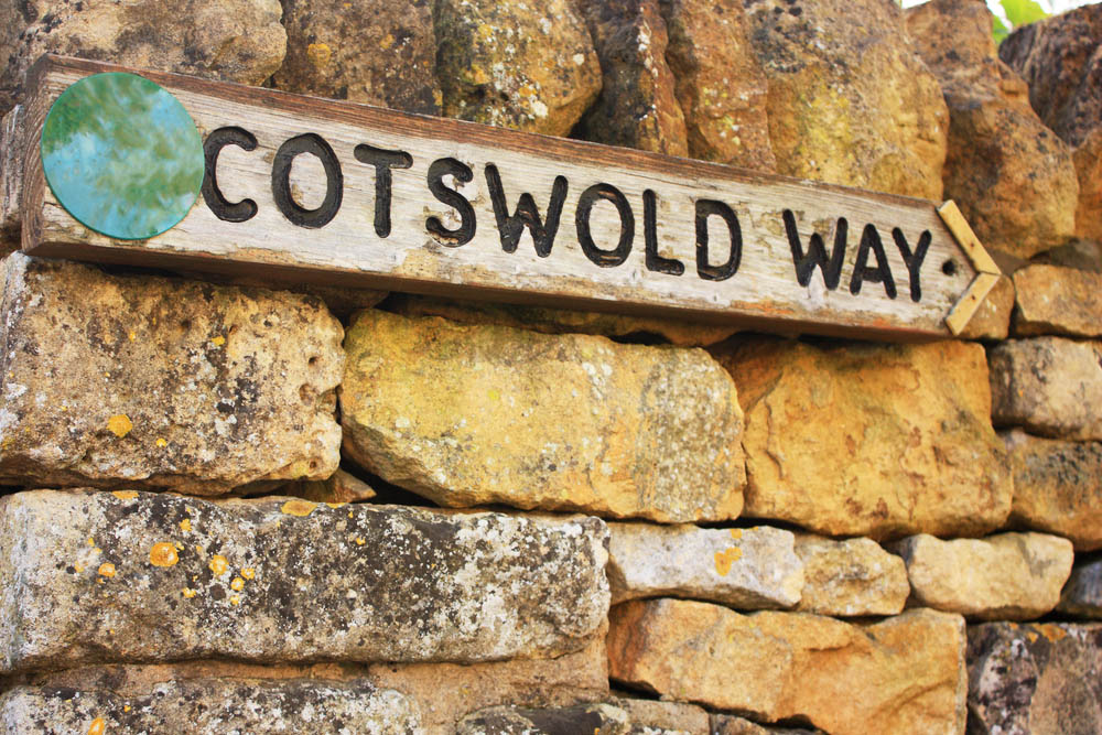 a sign on golden stone showing the path of the cotswold way walking route