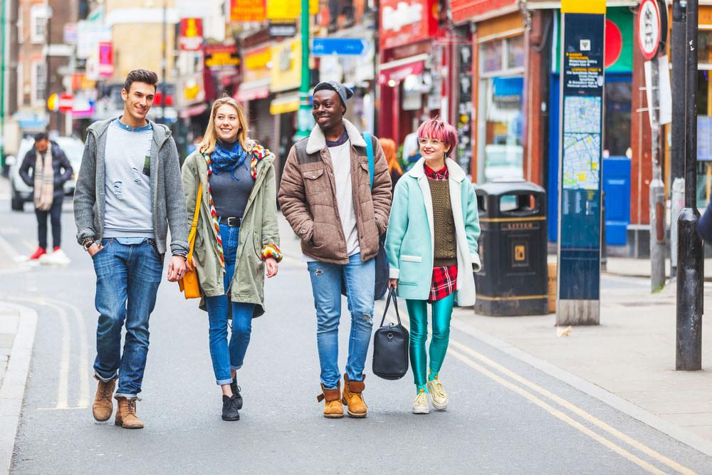 a young group walking down brick lane, london