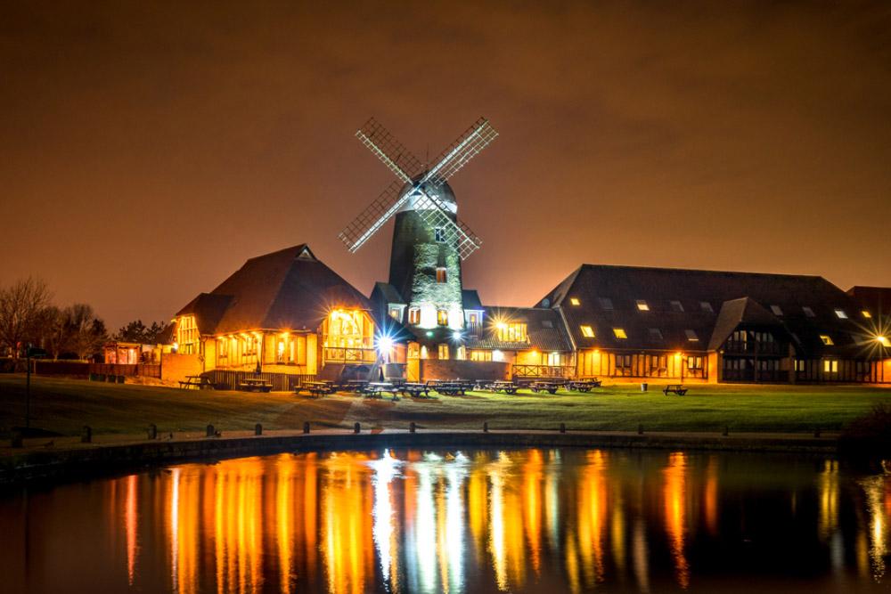 a windmill lit up at night on caldecott lake, milton keynes