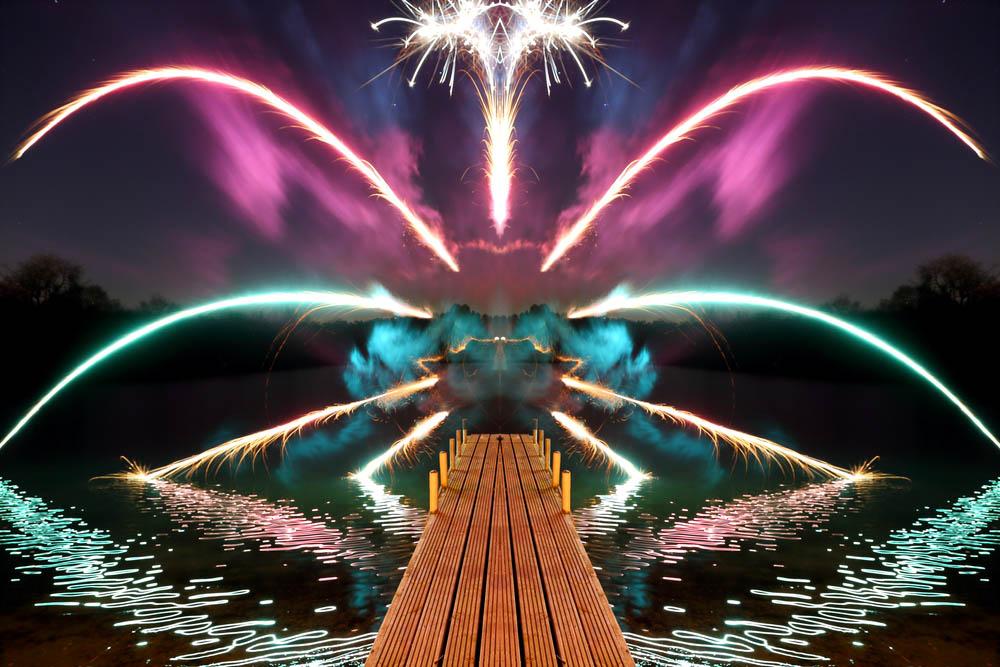 fireworks reflected in a milton keynes lake at dark