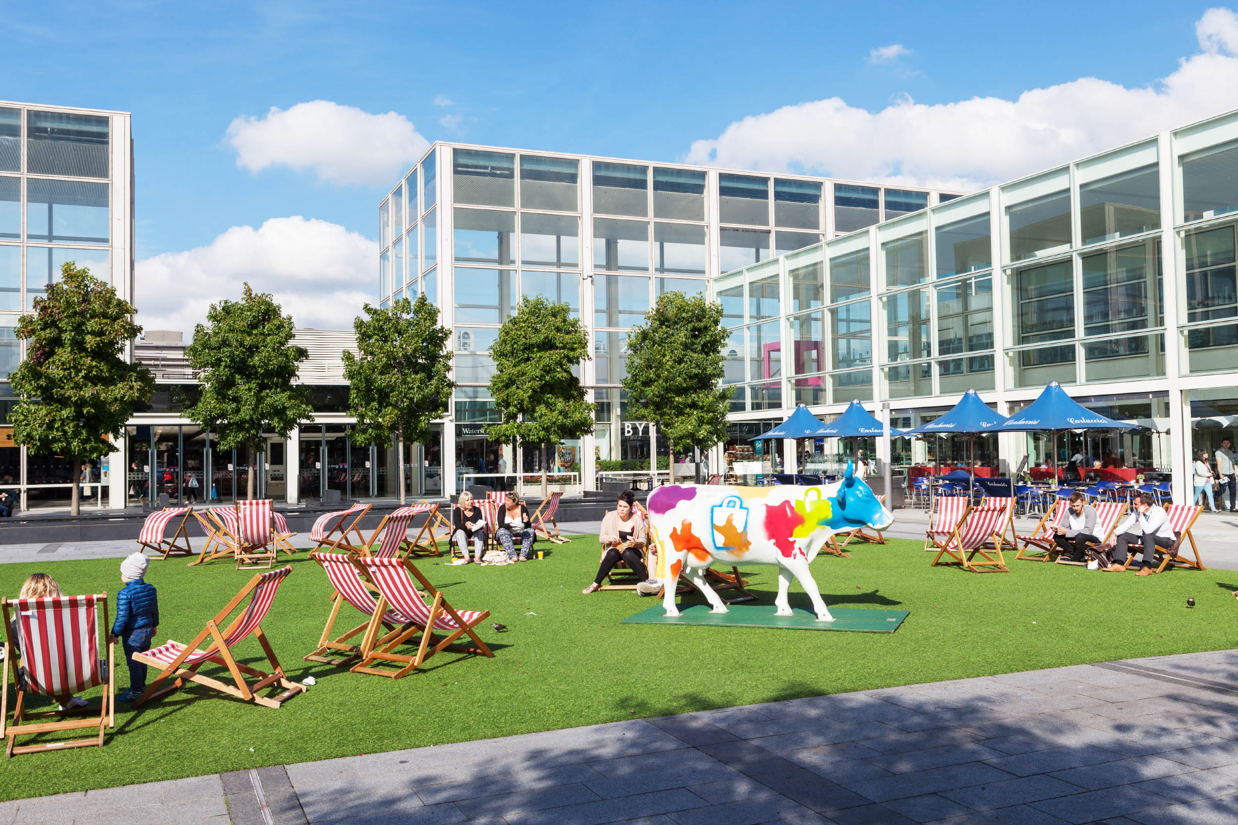 sunbathers at milton keynes shopping centre with colourful cow sculpture