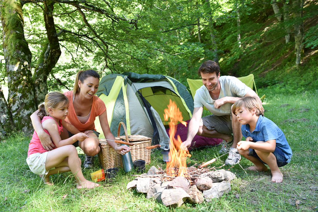 a family camping and roasting hotdogs outdoors