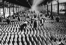 workers filling WWI munitions in a large warehouse around 1918